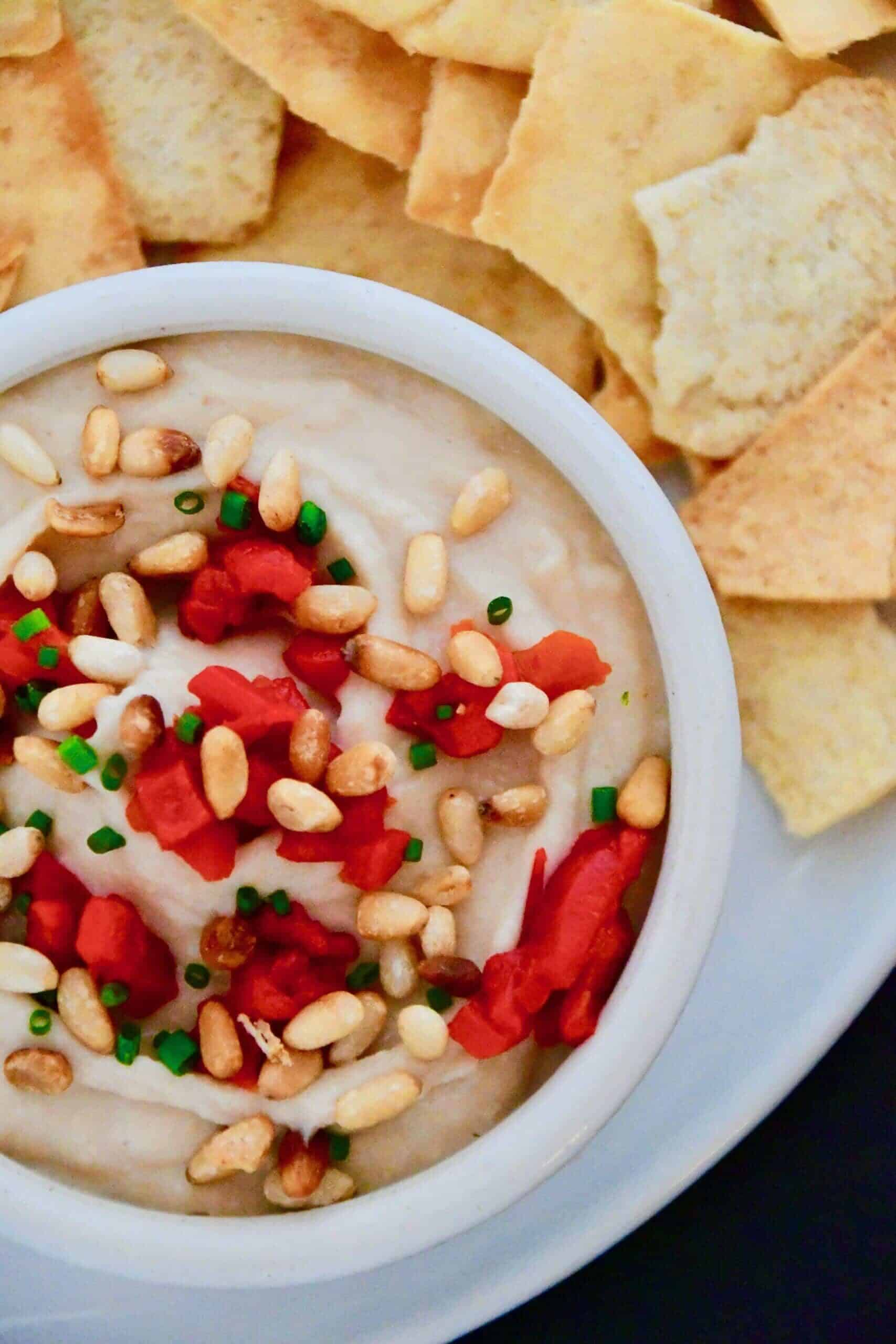 Joanna Gaines White Bean Hummus in a bowl topped with extra pine nuts and red peppers.