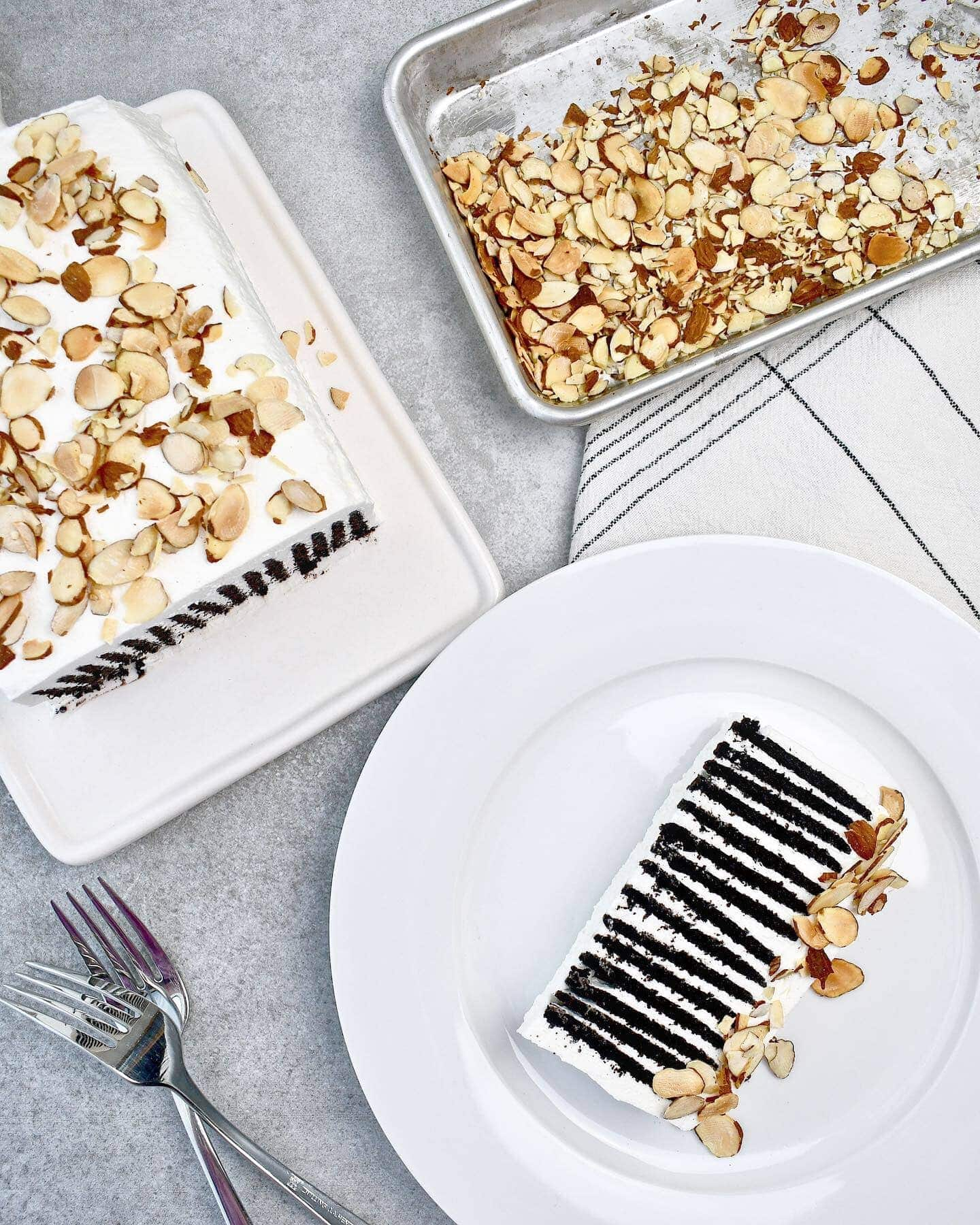 Chocolate Wafer Ice Box Cake, with a slice on a plate, an toasted almond in the corner.