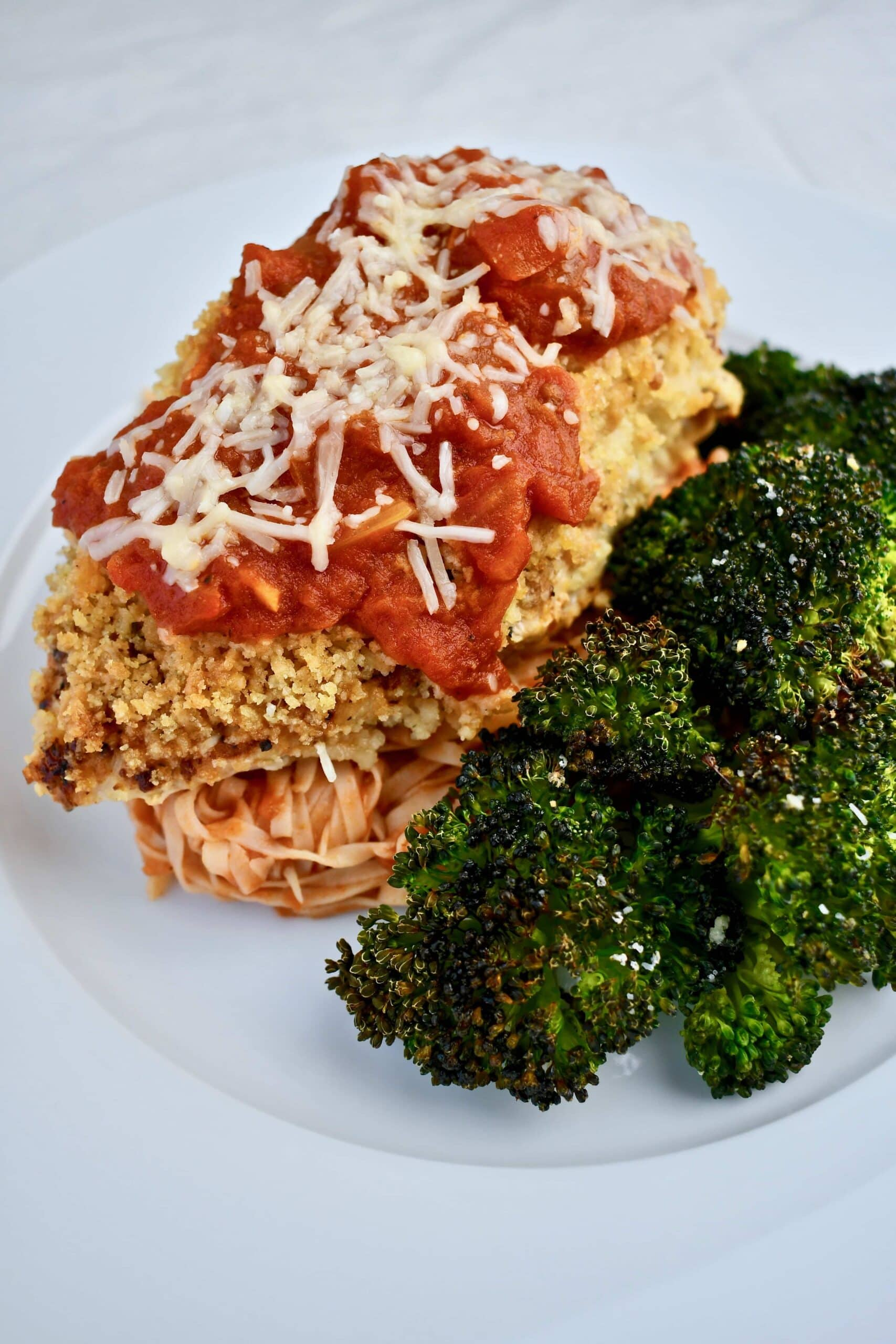 Chicken Parmesan, front view with a side of broccoli and pasta with sauce.