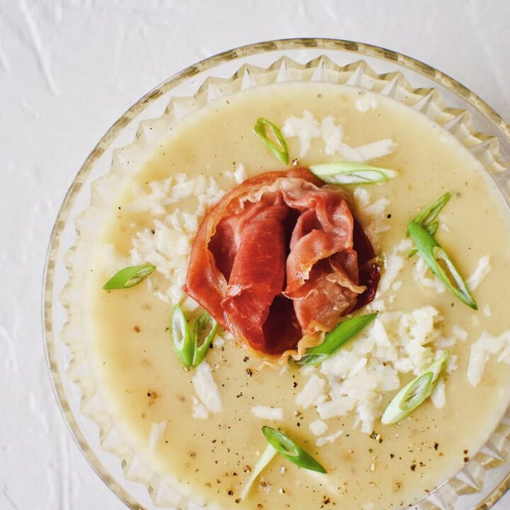 Creamy Potato Soup after blending, in a crystal bowl, topped with green onions, white cheddar, and a prosciutto rose.