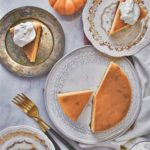 Whole sliced perfect pumpkin cheesecake on several plates on a table with pumpkins