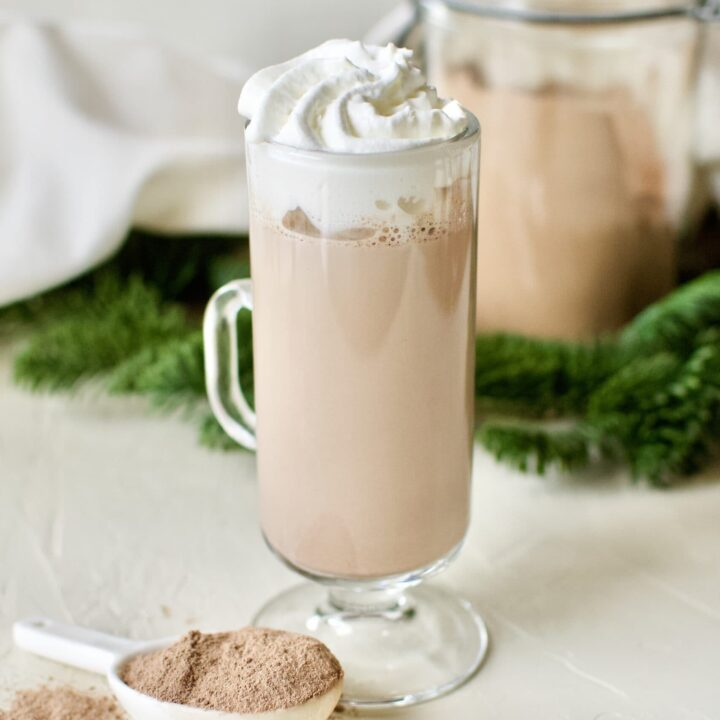 A glass of sugar-free hot cocoa topped with whipped cream.