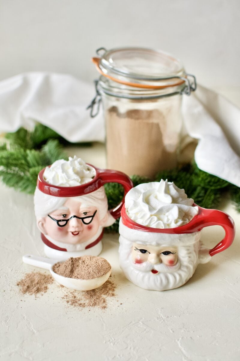A glass of sugar-free hot cocoa in Santa and Mrs. Claus mugs topped with whipped cream.