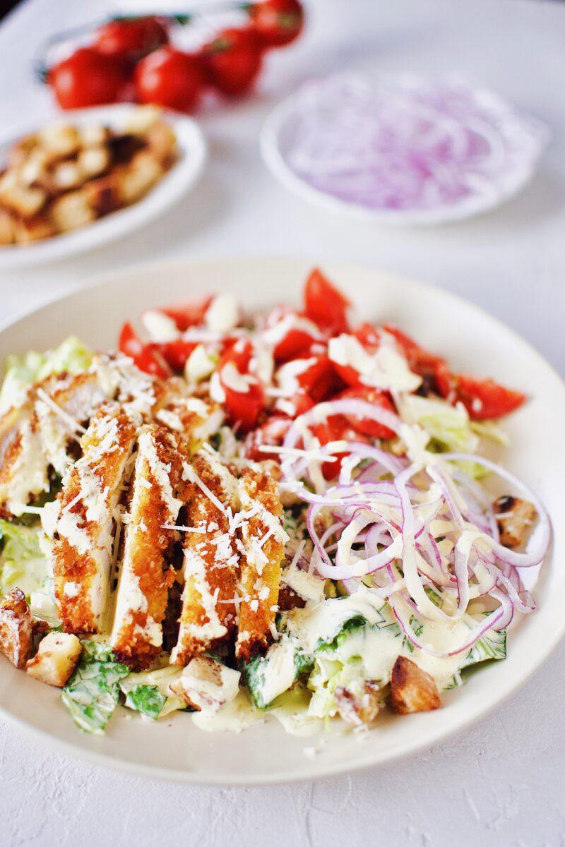 Creamy Caesar Dressing on a Crispy Parmesan Chicken Caesar Salad.