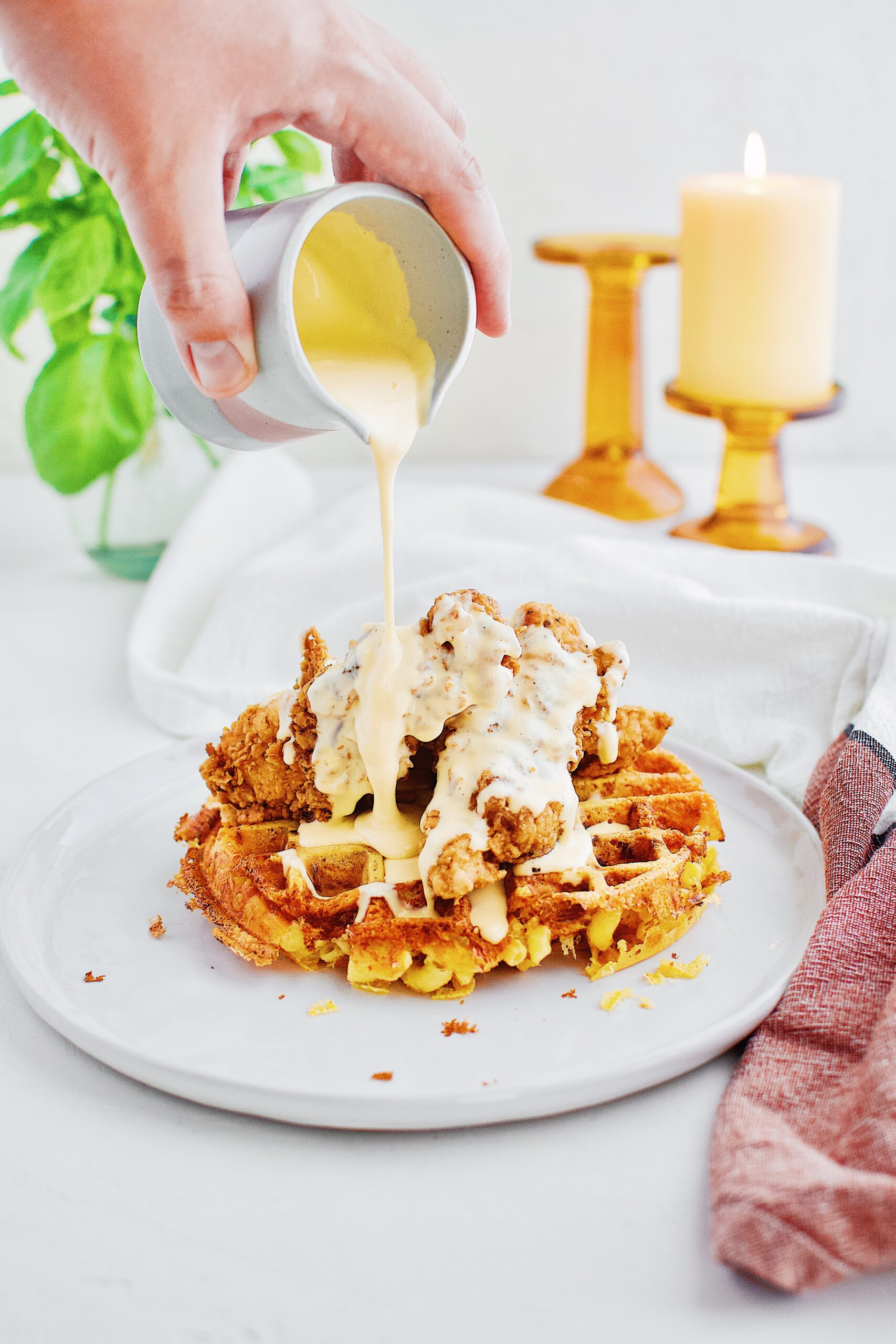 A hand pouring golden cheddar syrup over a stack of chicken mac n' cheese waffles on a white plate.