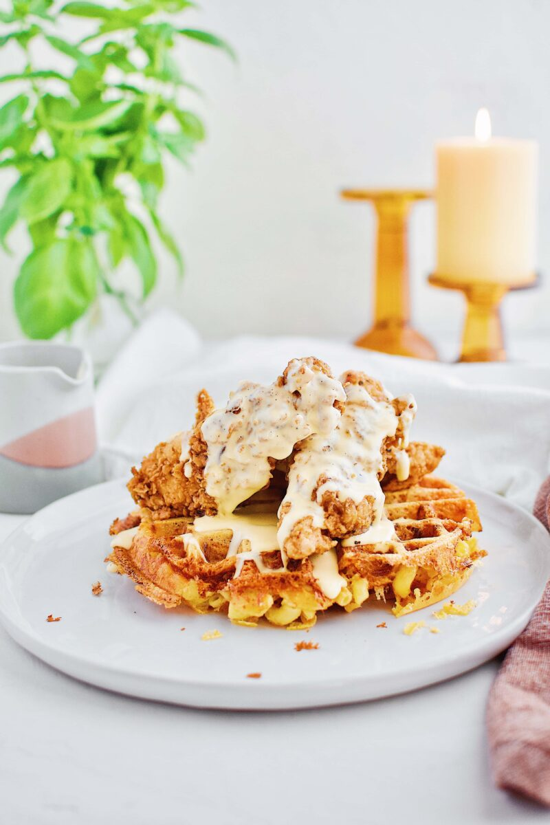 Waffle made of macaroni and cheese and topped with fried chicken and cheese syrup sauce