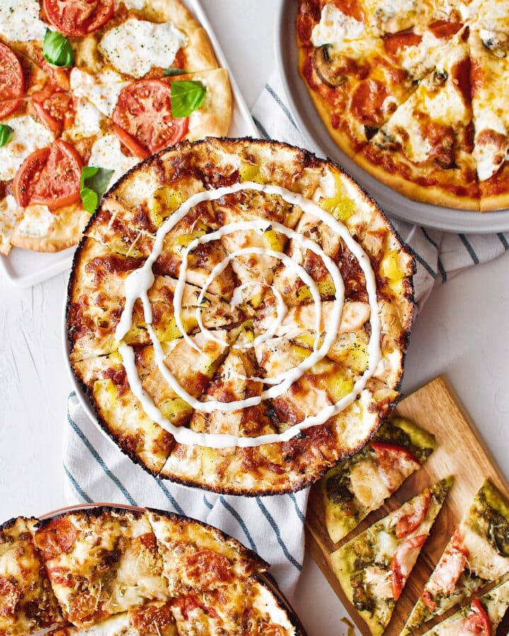 5 homemade pizzas on a table