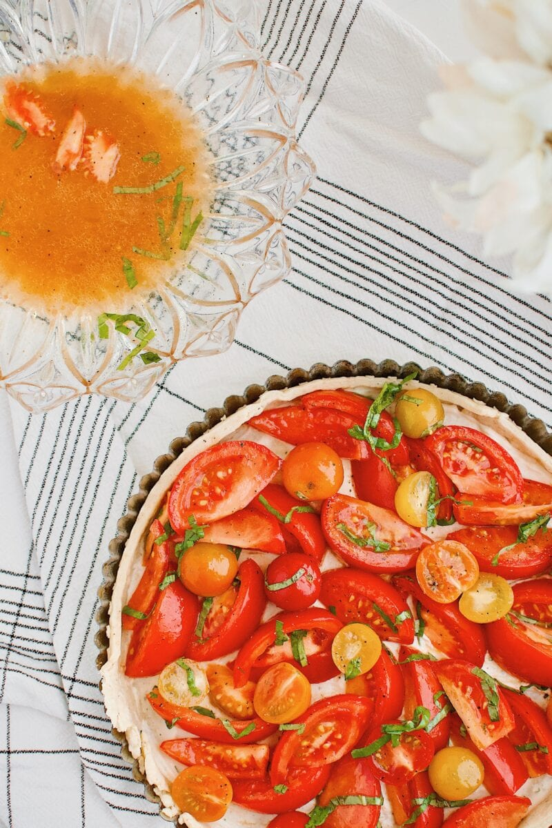tomatoes being placed in the tart shell