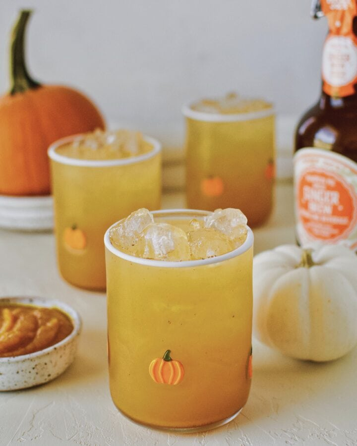 3 glasses of pumpkin juice in a row with baby pumpkin all around on a white background