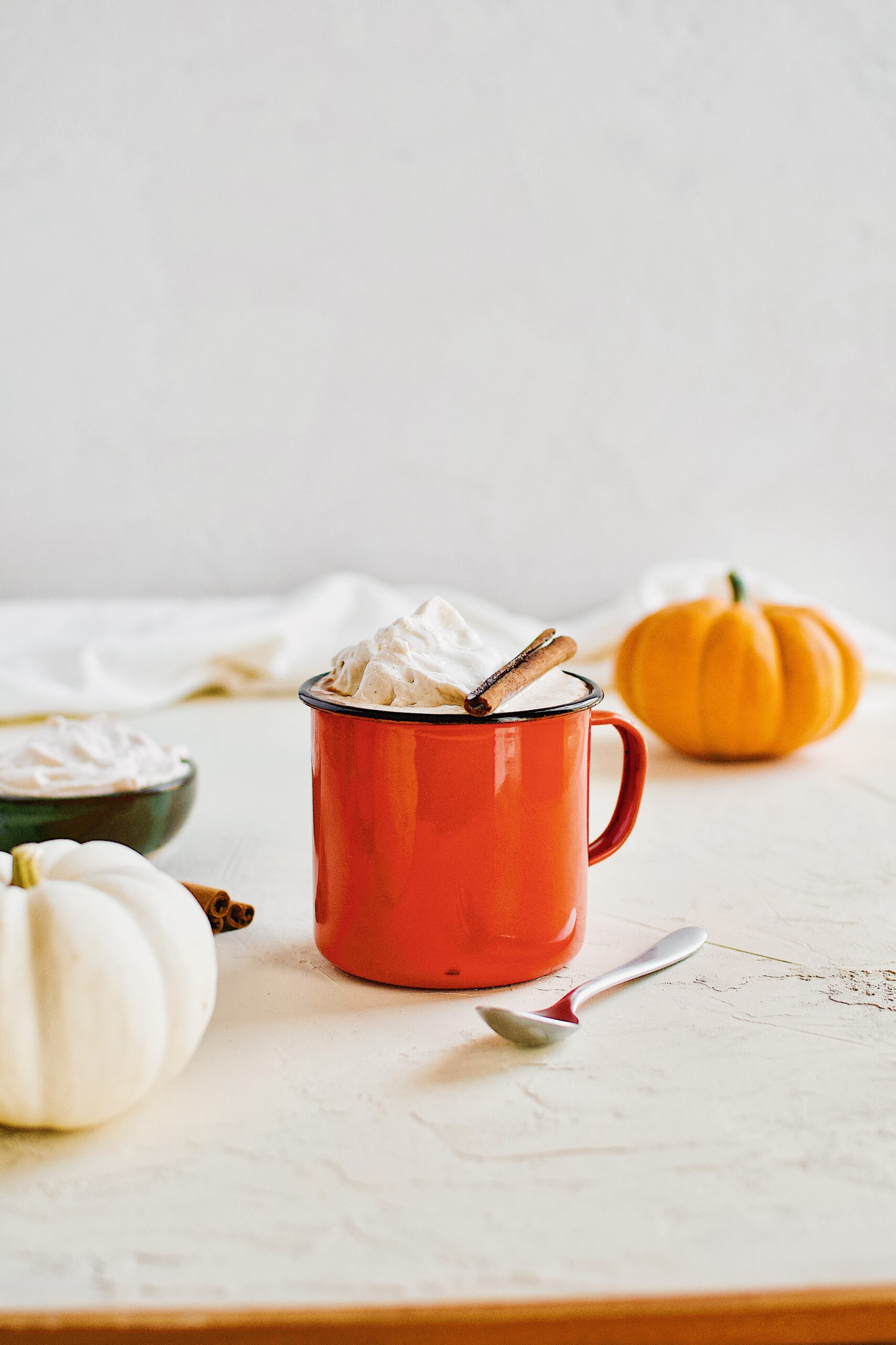 Pumpkin Spice Hot Chocolate in an orange camp mug topped with chai whipped cream and a cinnamon stick