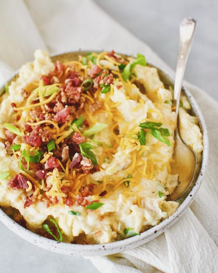 Loaded Baked Potato Mashers topped with bacon, cheese, and green onions in a serving bowl.