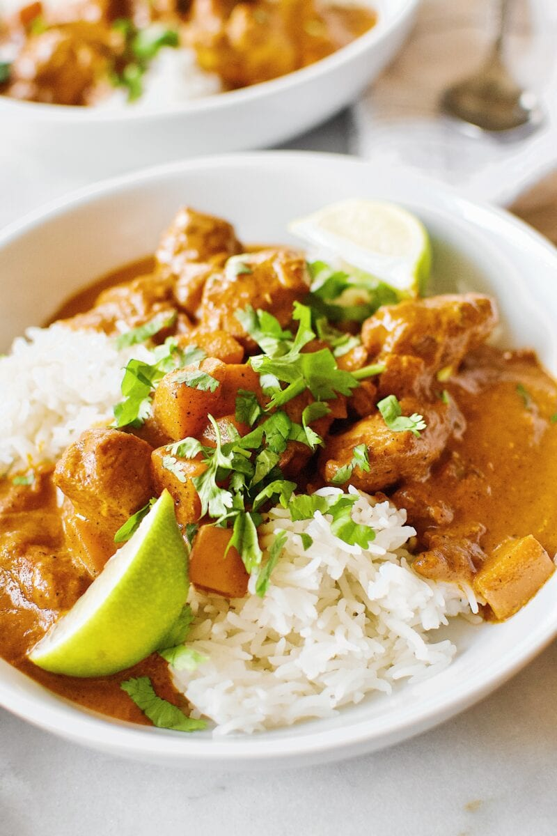 Pumpkin Butter Chicken served of basmati rice with cilantro and lime wedges.