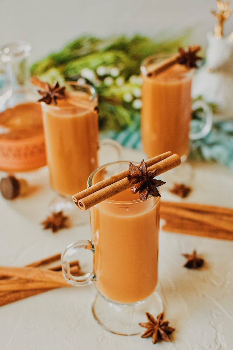 3 Winter Whiskey Wassail garnished with a cinnamon stick and star anise pod.