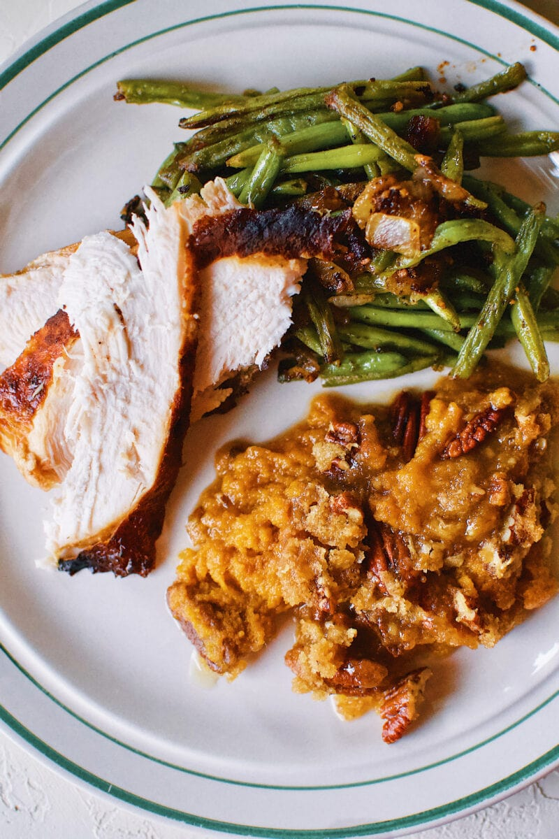 Great Aunt Sally's Sweet Potato Soufflé on a plate with Thanksgiving turkey and green beans.
