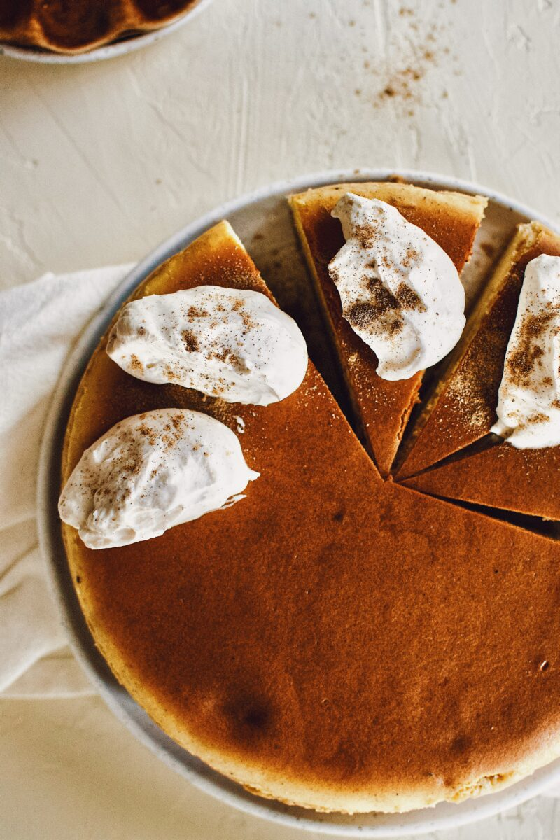 Chai-Spiced Cheesecake sliced and topped with Chai-Spiced Whipped Cream.