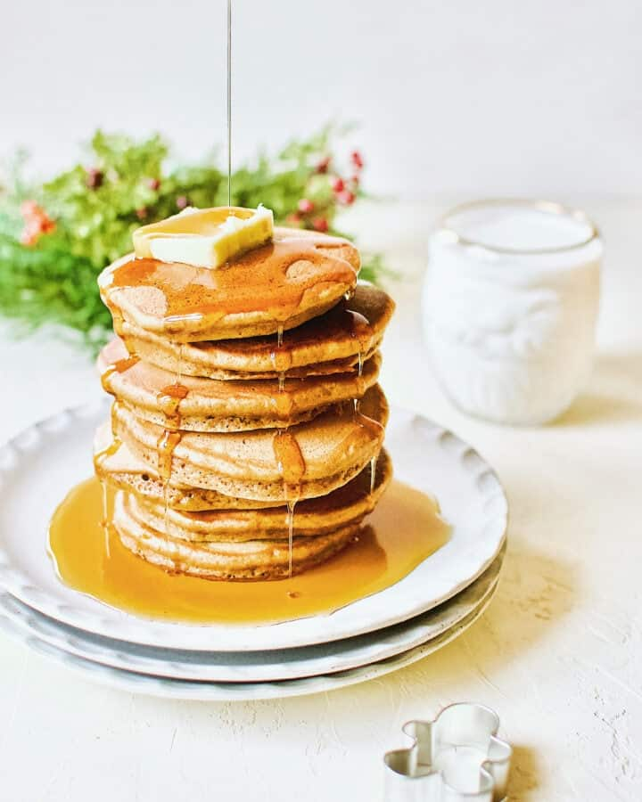 A stack of Gingerbread Pancakes topped with a pat of butter and maple syrup being drizzled over the top. A glass of milk sits in the corner in a santa shaped glass.