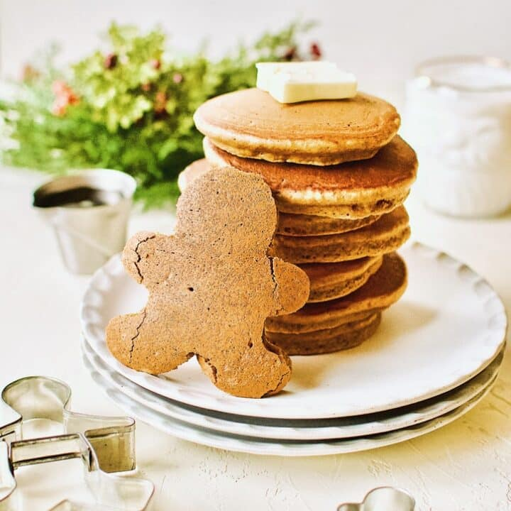 A stack of Gingerbread Pancakes with a Gingerbread Person shaped pancakes standing in front of the stack.