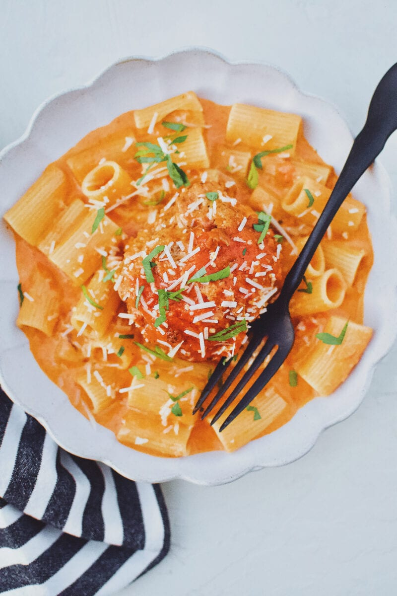 Giant Meatballs in Tomato Sauce served over Rigatoni Pasta and topped with parmesan and parsley.