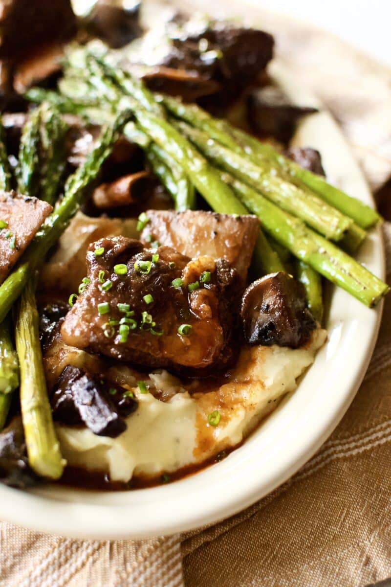 Red Wine Braised Short Ribs on a bed of mashed potatoes with broiled asparagus around them.