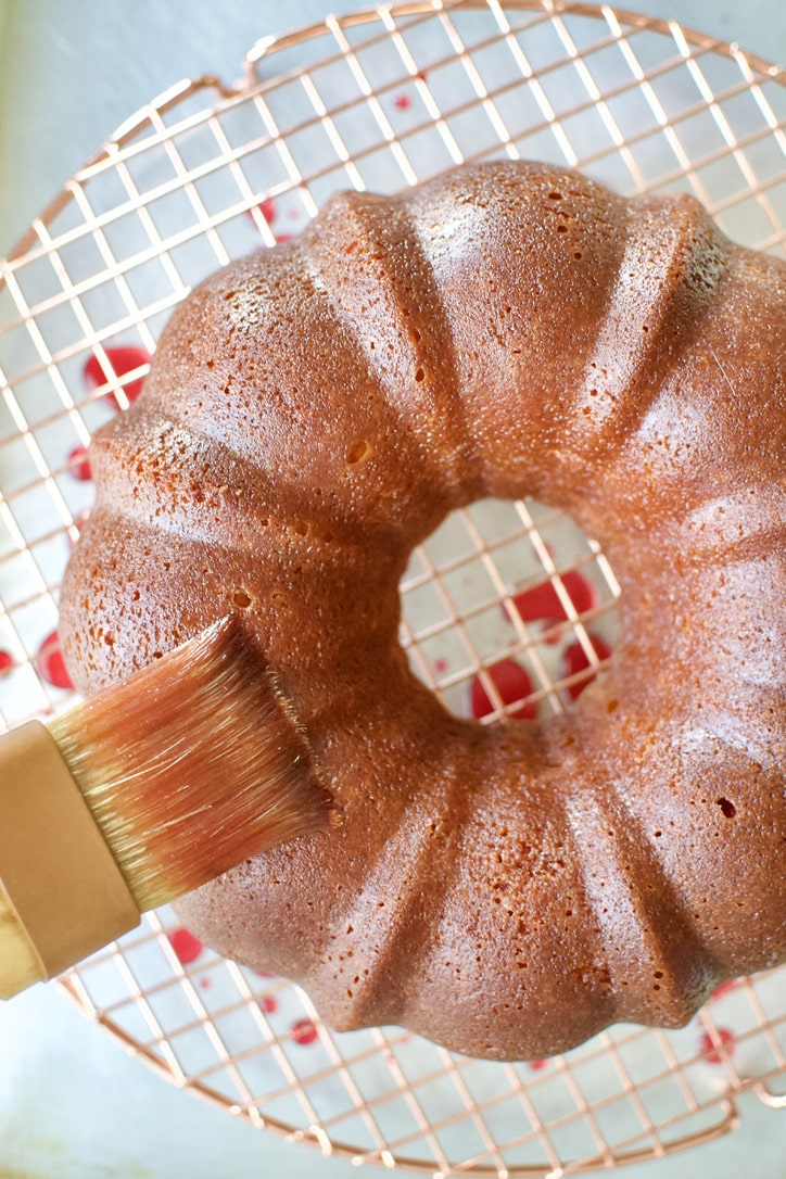 Brushing the freshly baked cake with blood orange simple syrup.
