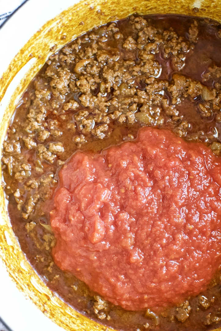 Adding crushed tomatoes to the pot to finish the chili.