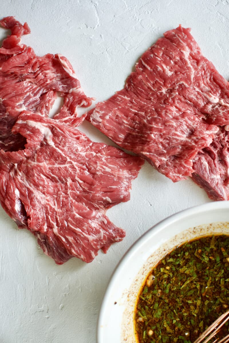 Beef Loin Flap Meat Steak and the Carne Asada Fajita Marinade in a bowl.