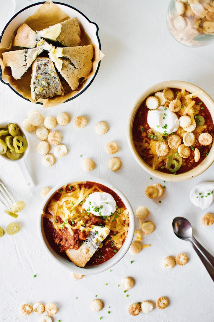 Spicy Texas Chili in two bowls surrounded by various toppings.
