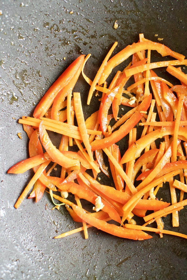 Carrots, Bell Peppers, and ginger cooking in a hot wok.