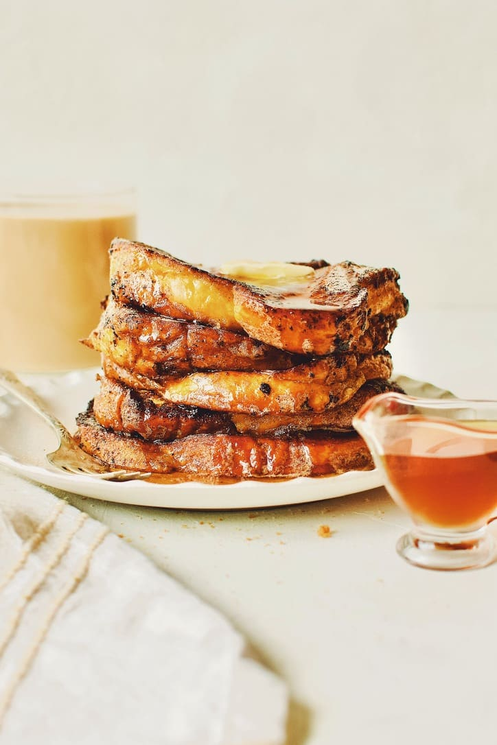 Finished French Toast sprinkled with cinnamon sugar, topped with butter, and drizzled with maple syrup.