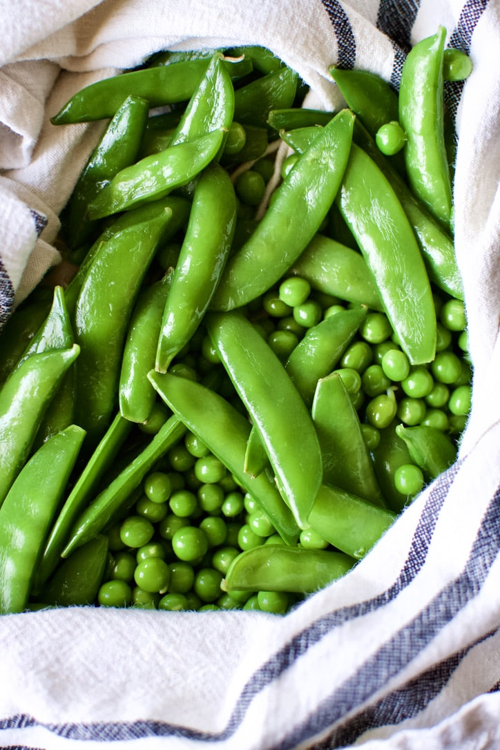 Drying the blanched and shocked sugar snap and english peas.