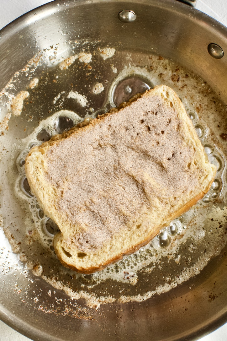 French Toast cooking on side one, side two dusted with cinnamon sugar.