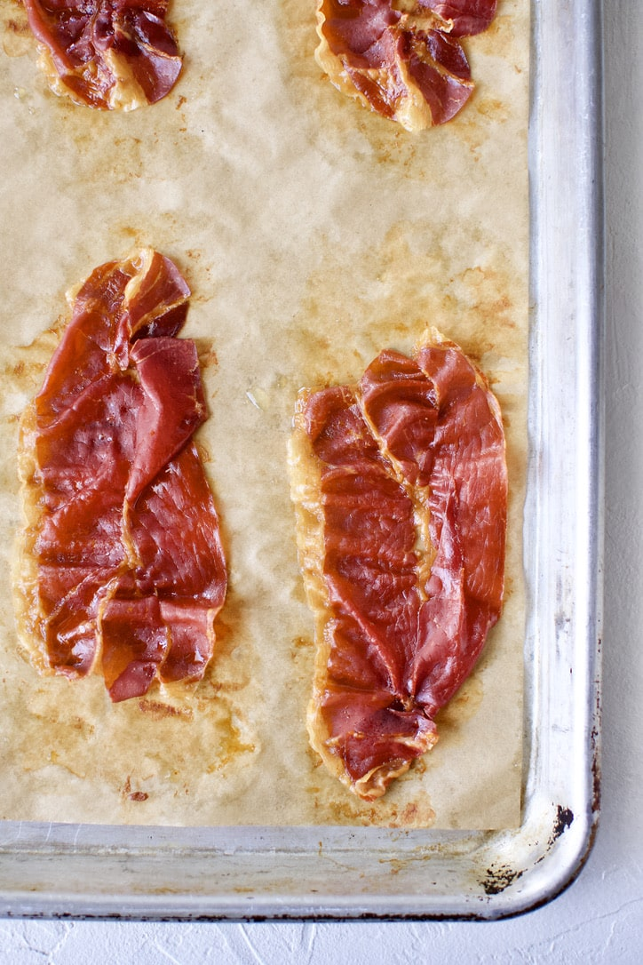 Crisp prosciutto on a parchment-lined baking sheet.
