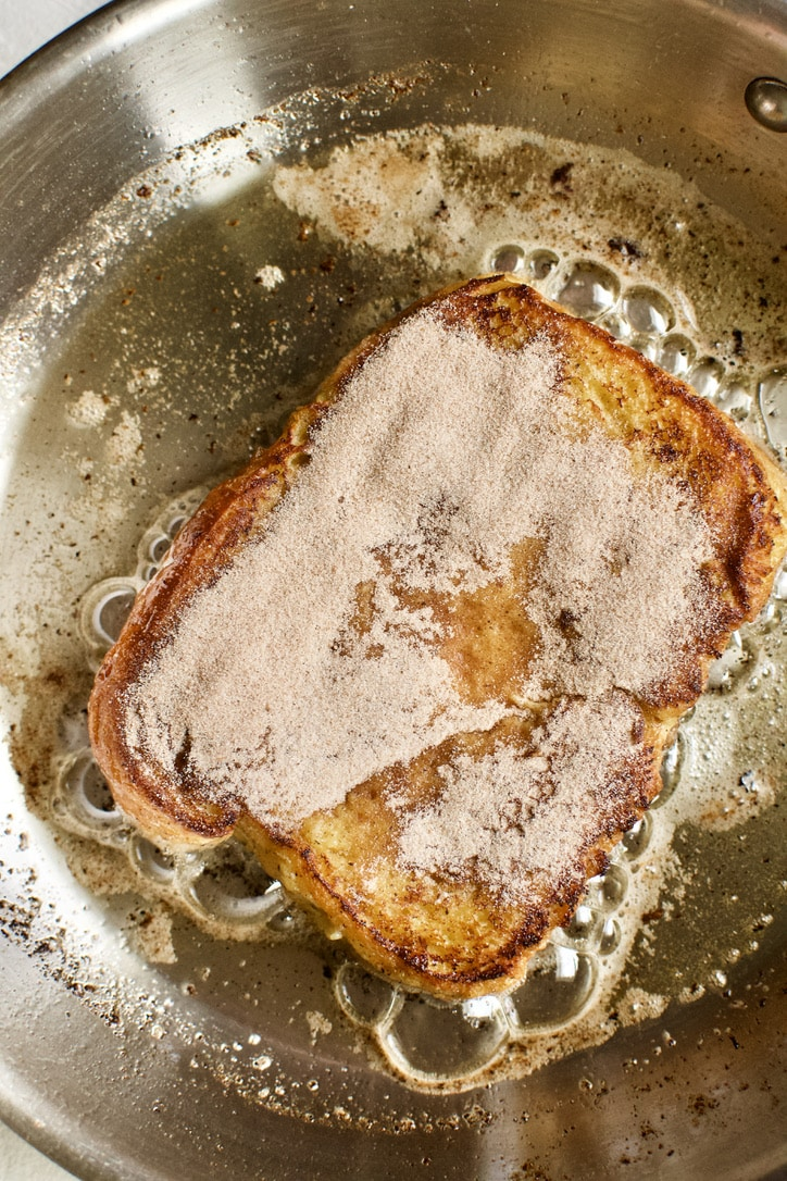 Flipped French toast with cinnamon sugar on side one.