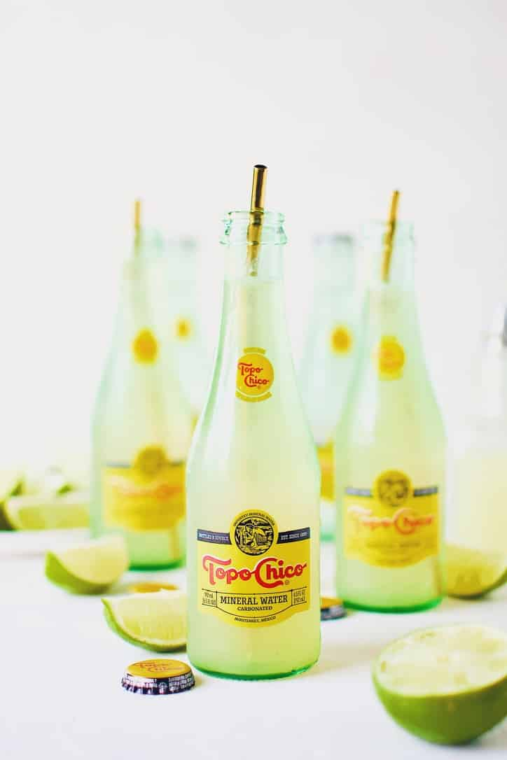 Topo Chico Margaritas bottled cocktails, surrounded by wedged limes.