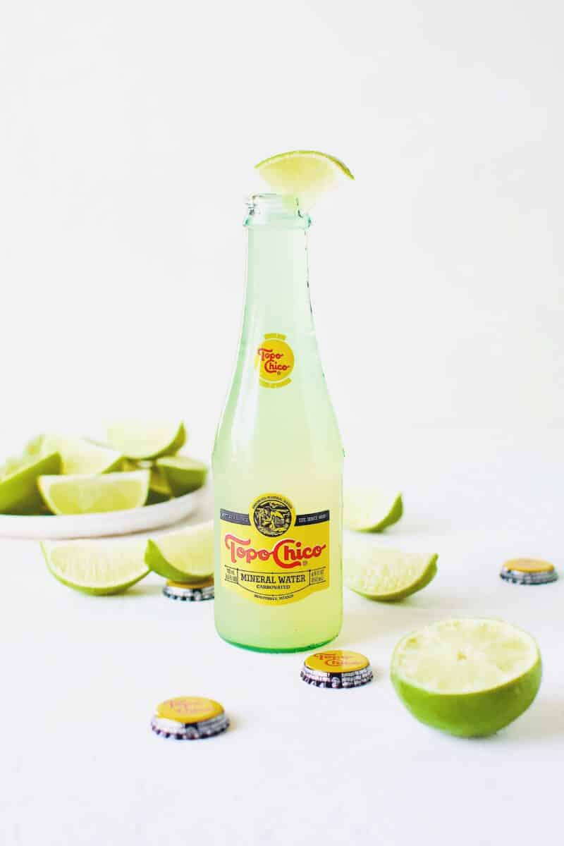 Topo Chico Margarita served in the bottle, surrounded by wedged limes.
