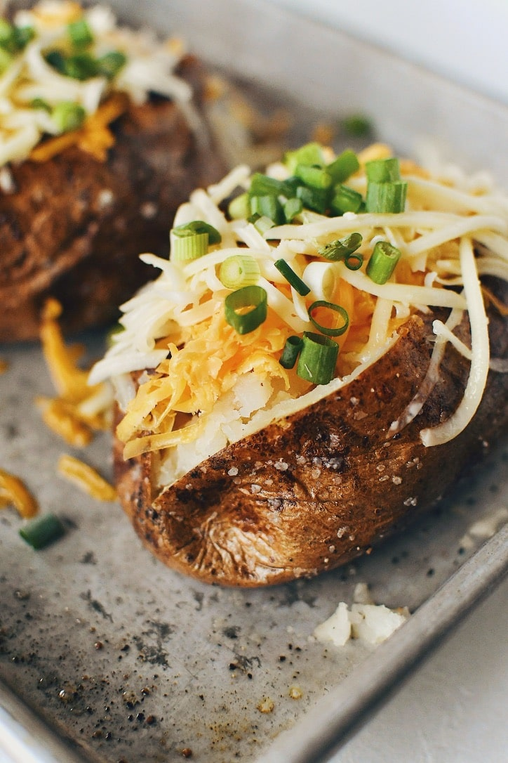 Crispy Skin Baked Potatoes topped with white and sharp cheddar cheeses and green onions.