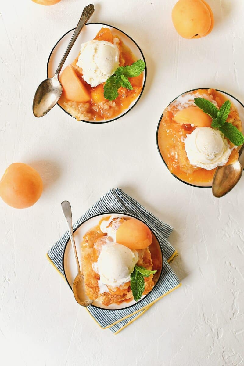 Apricot Cobbler served on small plates with a scoop of vanilla ice cream on top, a slice of fresh apricot, a sprig of mint, and a spoon to eat it with.