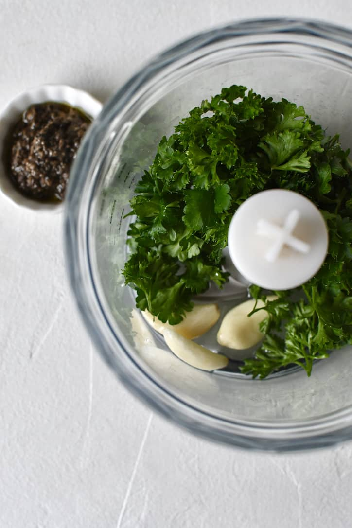 Garlic, parsley, and white truffle oil, together in a food processor ready to be blended together.