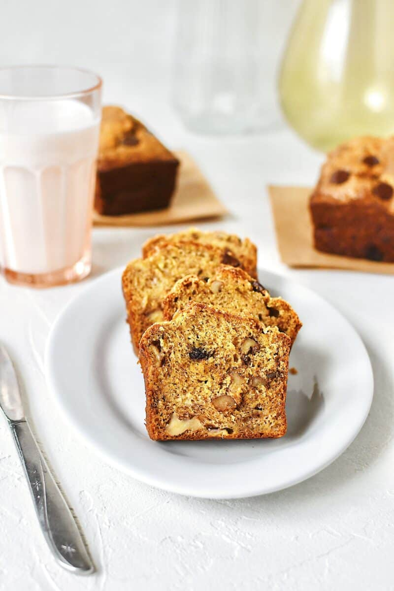 Slices of banana bread on a plate with a glass of milk nearby.