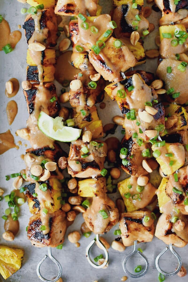 Pineapple Peanut Chicken Skewers fresh off the grill topped with peanut sauce, chopped green onions, and chopped peanuts.