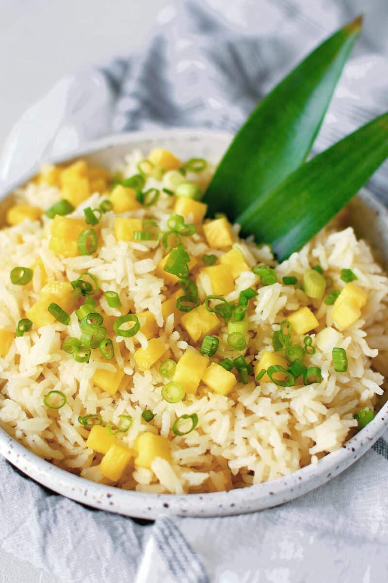 Pineapple Coconut Rice in a bowl topped with diced pineapple and green onions.