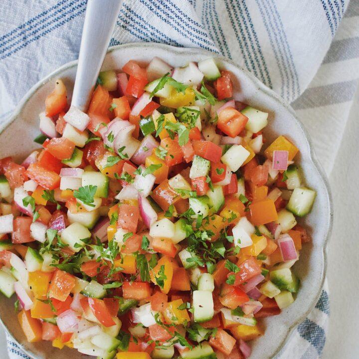 Greek Pico de Gallo in a bowl with a spoon.