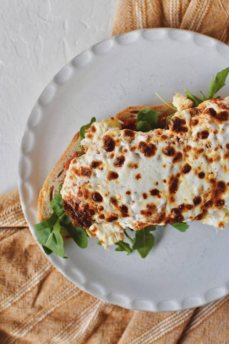 Building a Parmesan Chicken Sandwich, toasted bread with marinara sauce on top, a layer of arugula added, and crispy parmesan chicken on top that has mozzarella melted on it.
