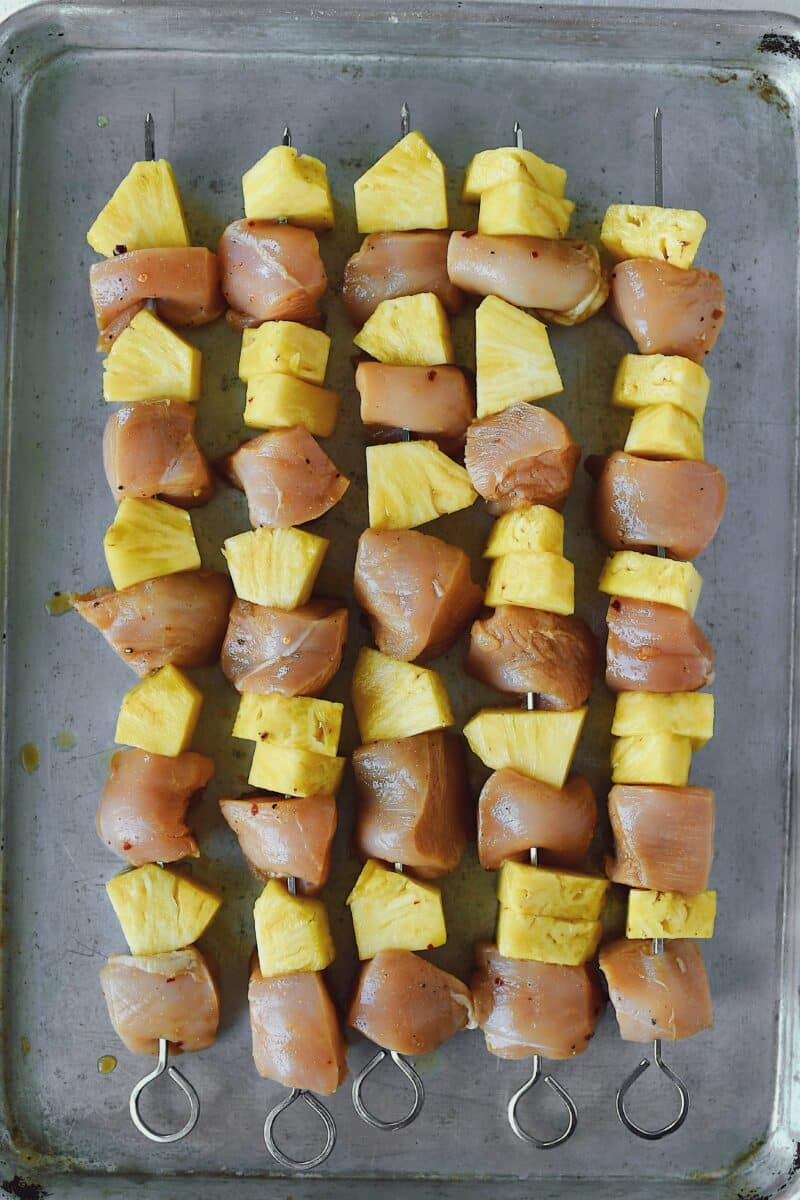 Marinated chicken and pineapple skewered and ready to be grilled.