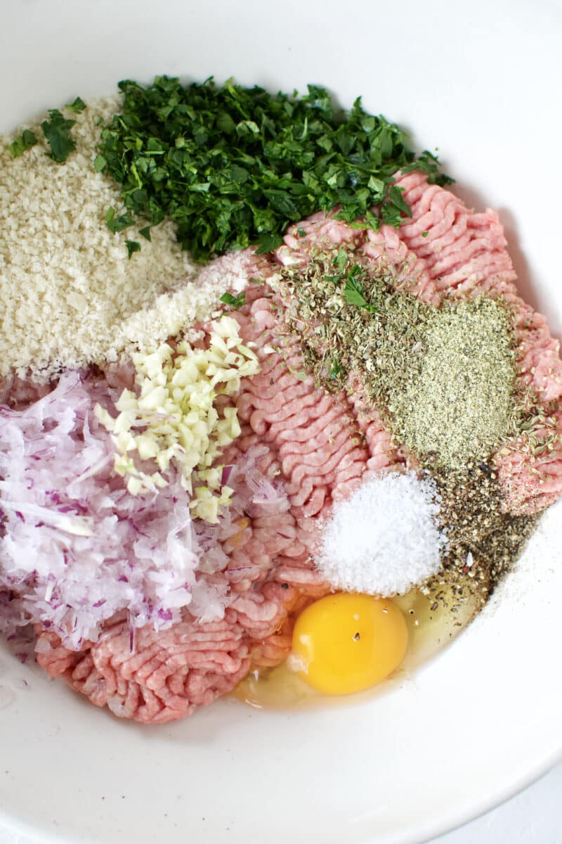 All the ingredients for Greek Meatballs together in a bowl before stirring to combine.