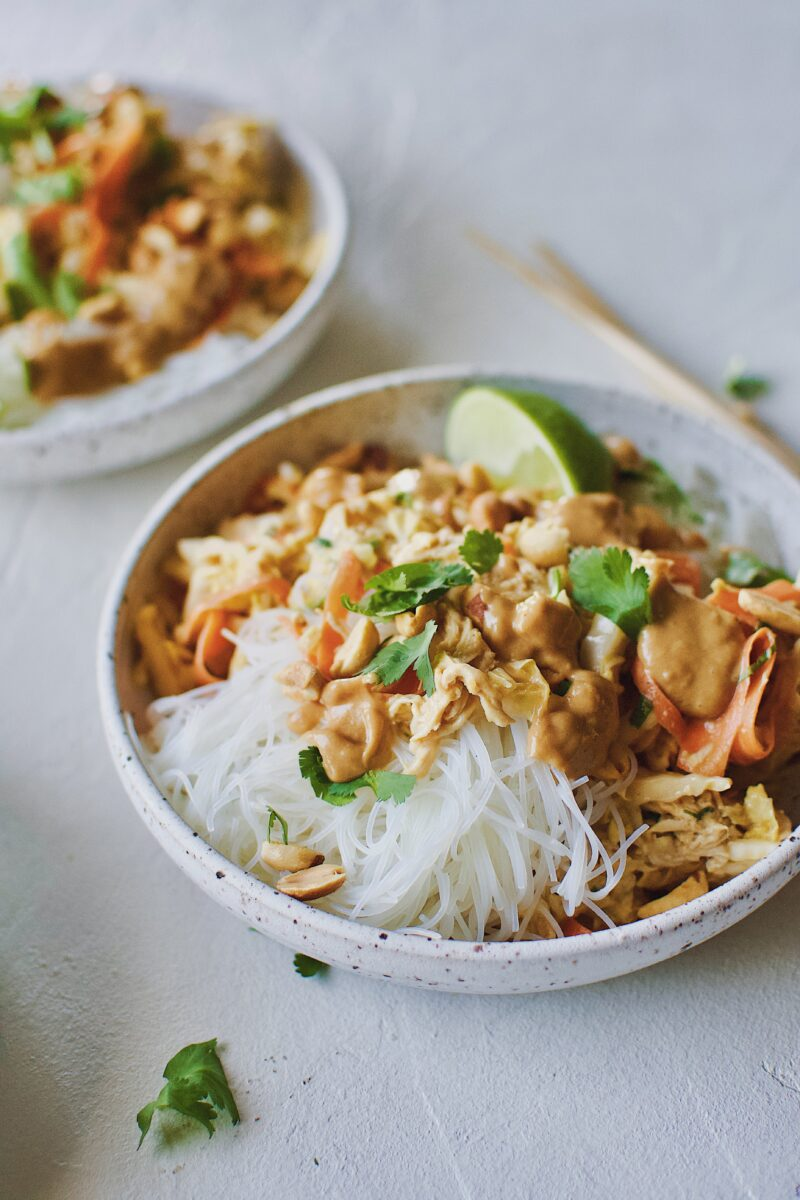 Asian Noodle Salad with Chicken in a noodle bowl and chopsticks on the side.