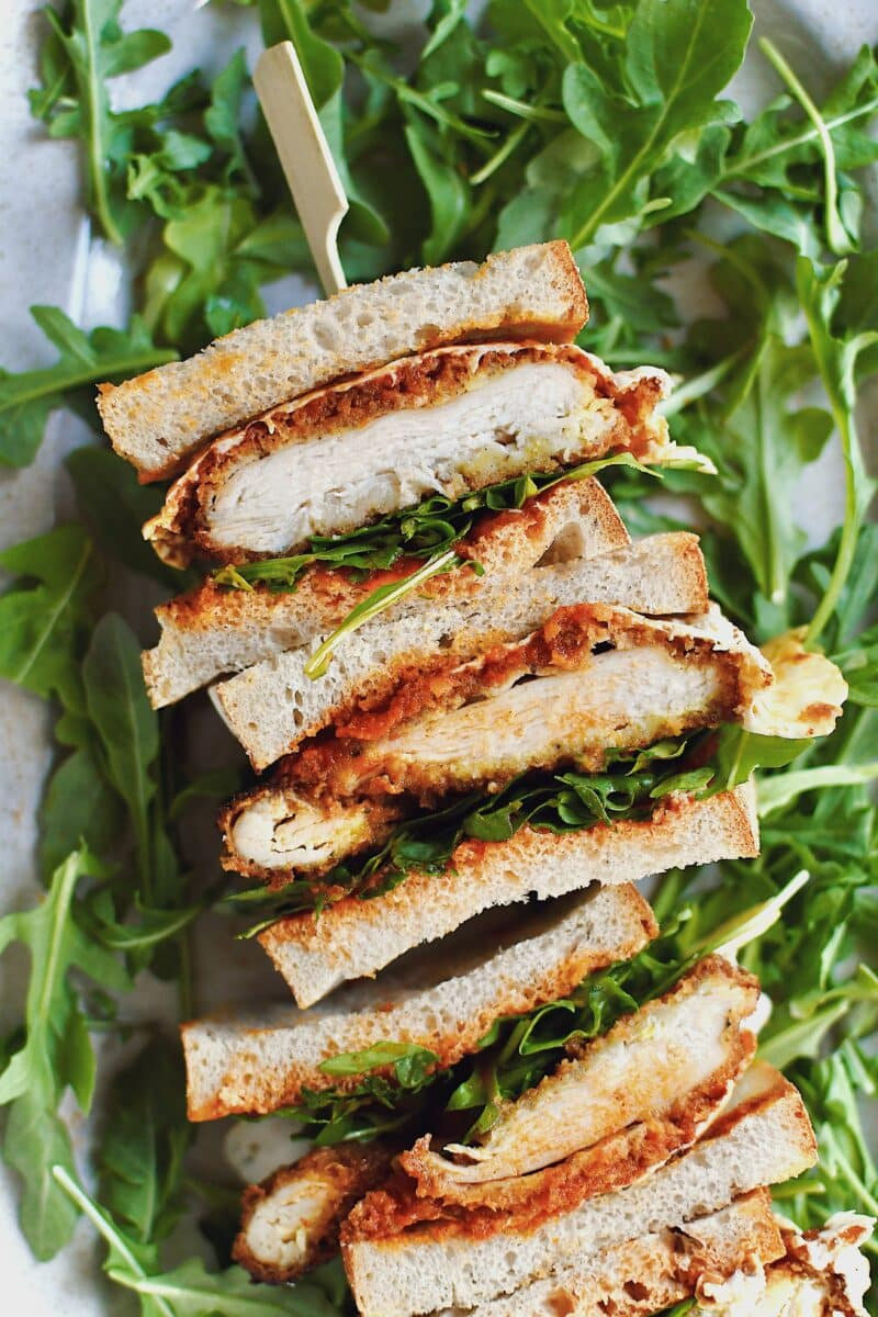 Parmesan Chicken Sandwich, sliced and stacked, laid on a platter on a bed of arugula.