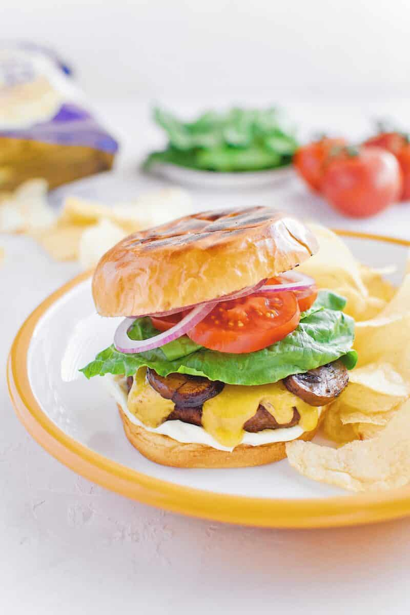 """Not-So """"Basic"""" Burger stacked up on a plate with chips and my favorite toppings."""