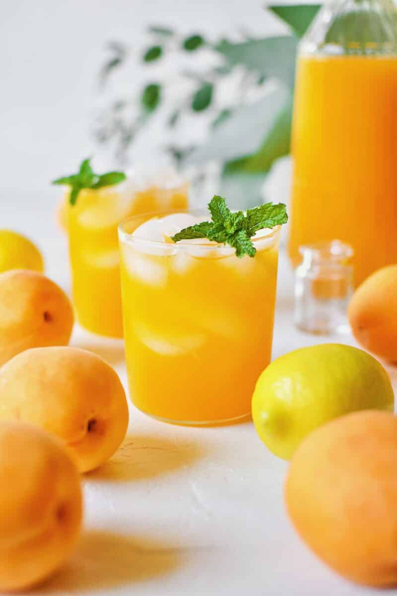 Apricot Nectar Juice in a glass with ice, surrounded by fresh apricots and lemons, with a pitcher of apricot juice in the background.