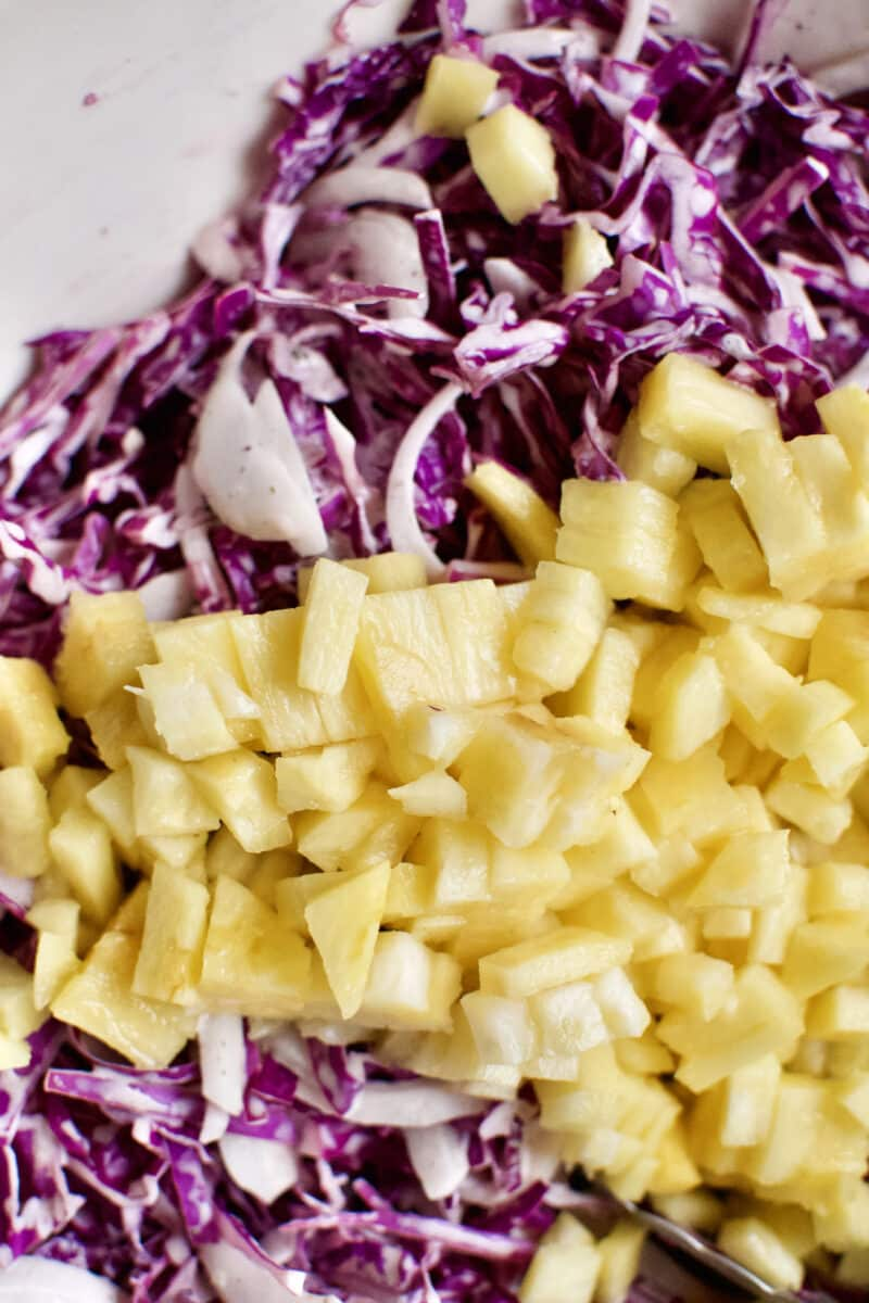 Adding the pineapple to the red cabbage slaw.